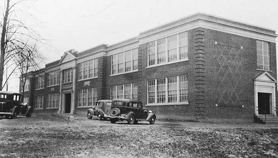 Black and white photograph of the old Fairfax High School taken in 1935. The building is two stories tall with six large banks of windows on both floors. The main entrance is ornately designed with columns. Early 1930s era cars are parked in front of the building.