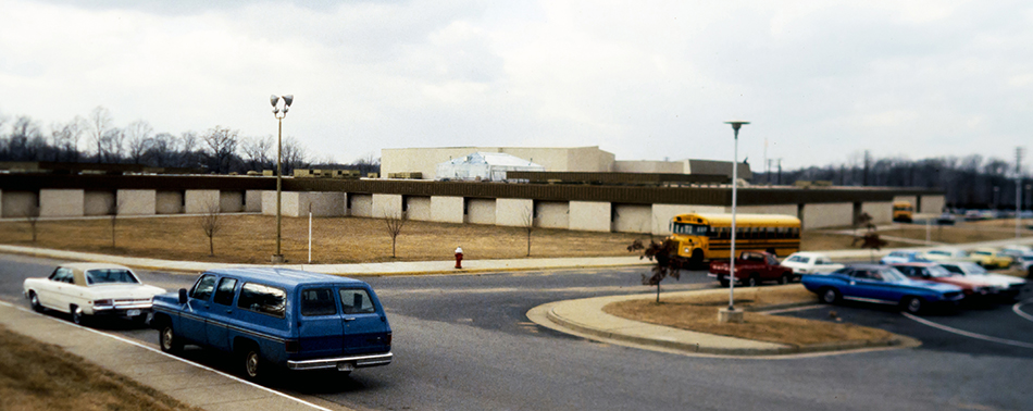 Undated color photograph of the new Fairfax High School taken from the hillside along Old Lee Highway. In the foreground are several cars and a school bus which, by their makes and models, appear to date this photo to the late 1970s or early 1980s.
