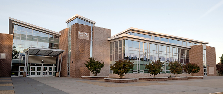 Entryway of the newly renovated Fairfax High School. The building has a very modern look with angled roof sections and large glass windows running the length of the front. The photograph was taken shortly after sunrise and there is a pink glow on the windows.